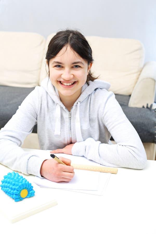 Het doen van thuiswerk Het schoolmeisje schrijft nota's stock foto's