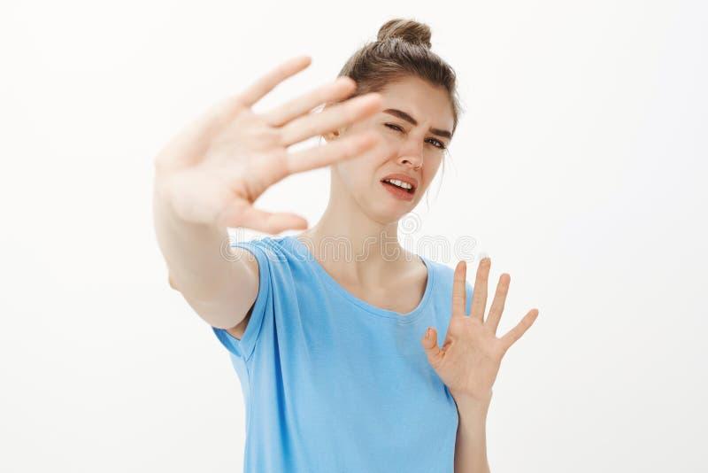 Het is doend walgen, einde Portret van intense ontstemde en weerzinwekkende vrouw in blauwe t-shirt die palm naar camera trekken royalty-vrije stock fotografie
