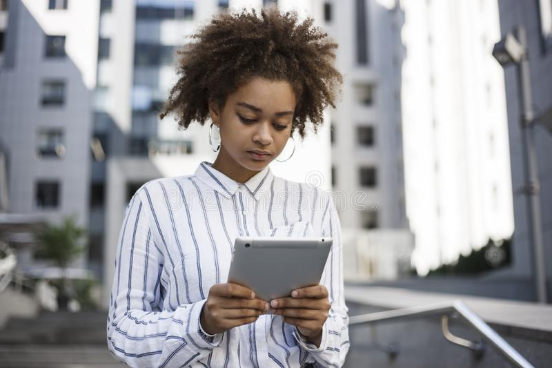 Het donker-gevilde meisje houdt een tablet in haar handen en werkt aan het Zij bevindt zich dichtbij een bureaugebouw op de straa royalty-vrije stock afbeeldingen