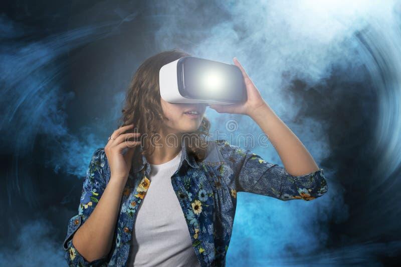 Het donker-haired meisje kijkt in glazen van virtuele werkelijkheid, abstract beeld, blauwe gradi?nttonen royalty-vrije stock afbeelding