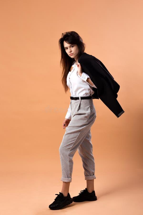 Het donker-haired meisje kleedde zich in wit overhemd, grijze broeken en zwarte tennisschoenentribunes met het zwarte jasje op ha royalty-vrije stock afbeelding