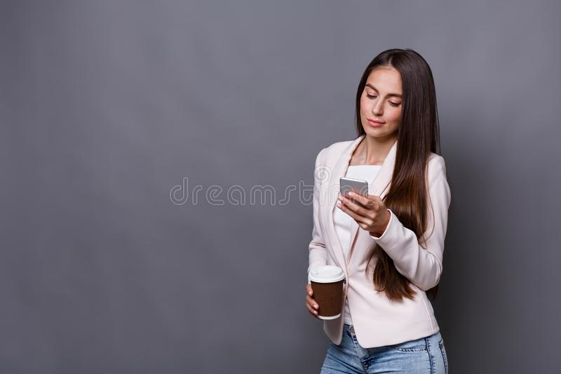 Het donkerbruine bedrijfsvrouw texting op mobiele telefoon en het drinken koffie op het werk royalty-vrije stock afbeeldingen