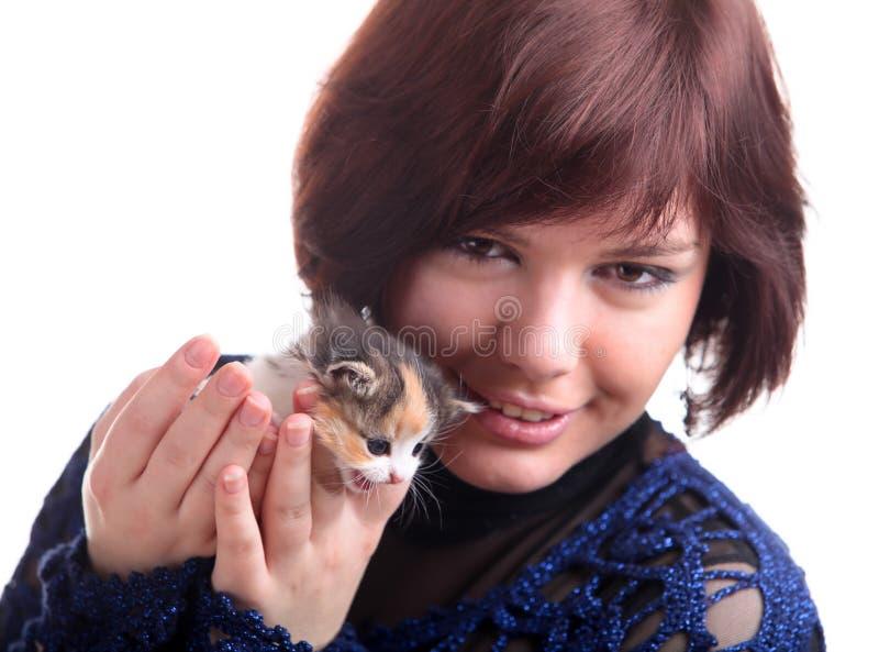 het donkerbruine kortharige meisje in kantkleding houdt katje stock foto's