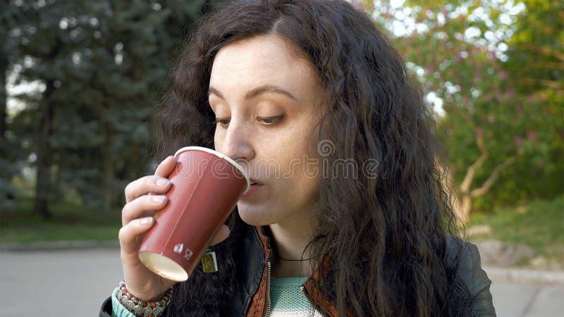 Het donkerbruine lange portret van het haarmeisje in openlucht met thee stock fotografie