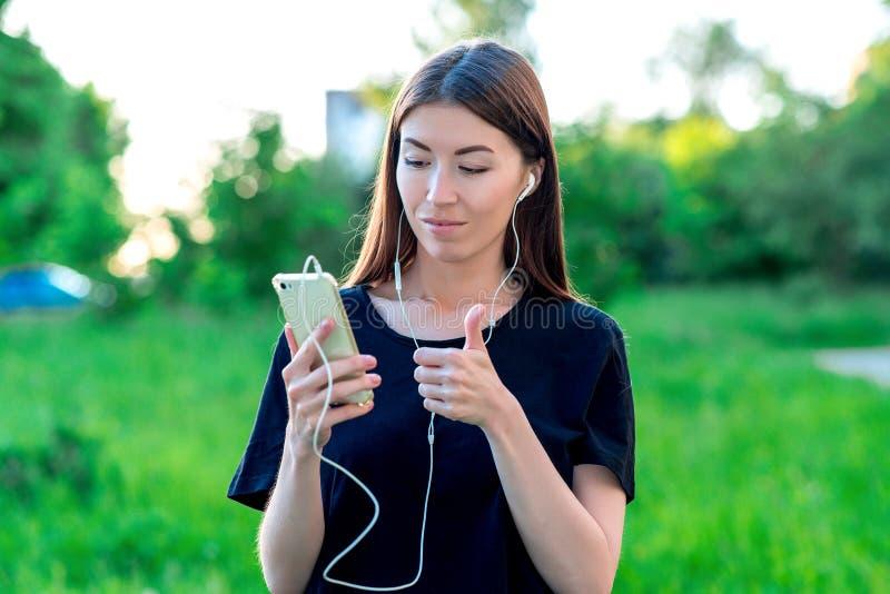 Het donkerbruine meisje in de zomer in een park op aard Een videovraag communiceert over telefoon Houdt handen met een telefoon m stock foto
