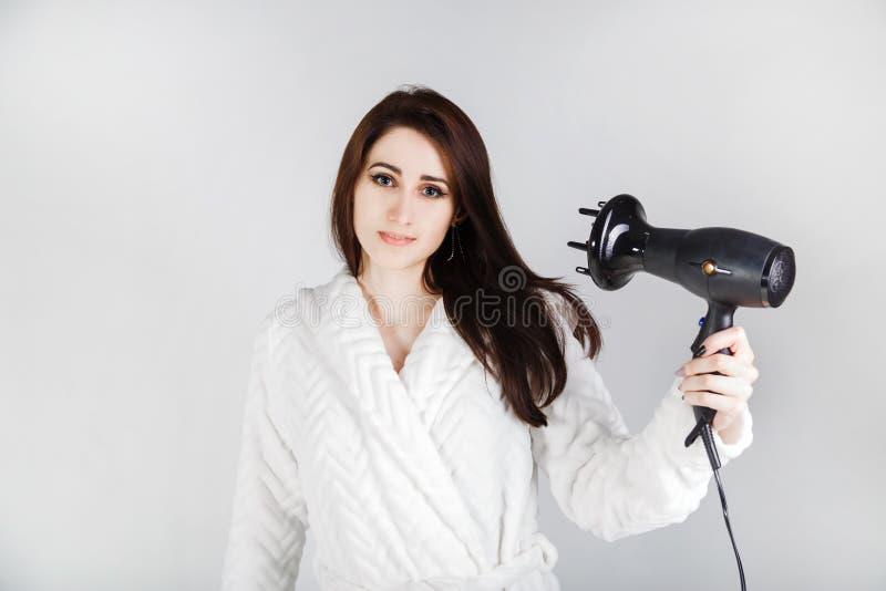 Het donkerbruine meisje in een badjas met een droogkap droogt haar haar tegen een lichte achtergrond royalty-vrije stock fotografie