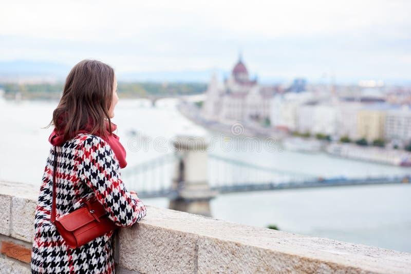 Het donkerbruine meisje geniet van mening van het Hongaarse Parlement in Boedapest royalty-vrije stock afbeelding
