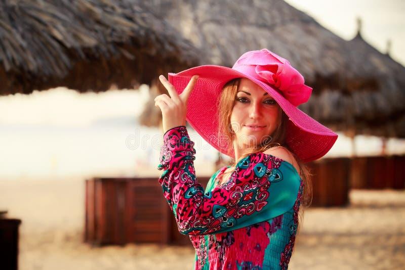 het donkerbruine meisje in grote rode hoedenglimlachen bij defocused paraplu royalty-vrije stock foto
