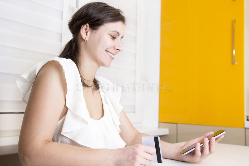 Het donkerbruine meisje houdt smartphone en plastic creditcard in haar hand de buigende jonge vrouw verricht online betalingen stock foto