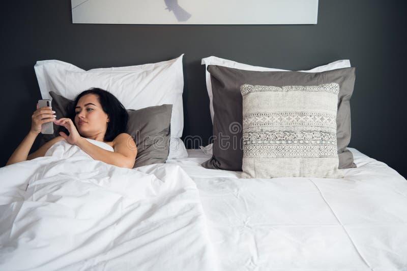Het donkerbruine meisje leest tekstbericht van haar vriend op mobiel, terwijl in het bed ligt Vrolijke Jonge Vrouw royalty-vrije stock afbeelding