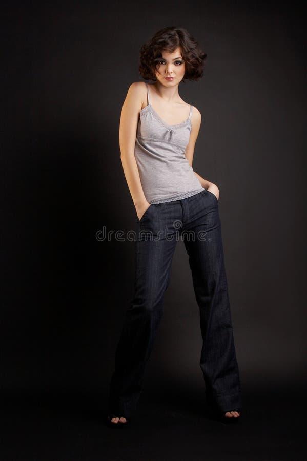 Het donkerbruine meisje stellen op donkere achtergrond stock foto's