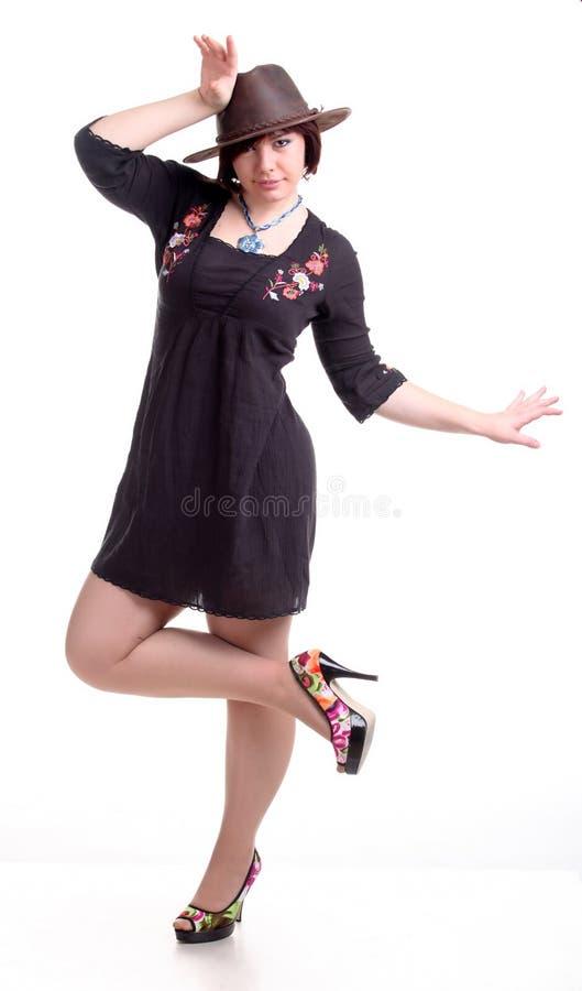 het donkerbruine meisje stelt in zwarte kleding en hoed stock afbeelding
