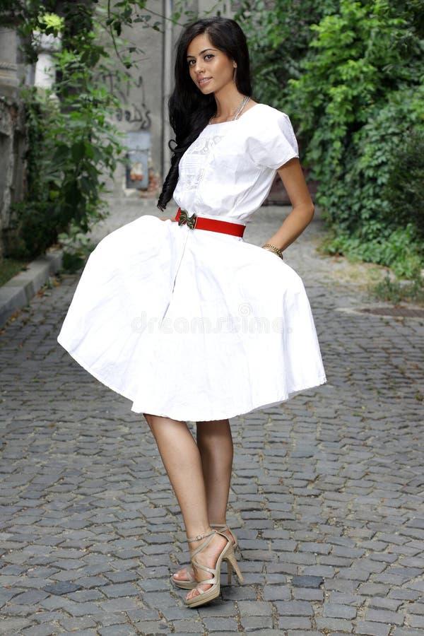 Het donkerbruine meisje van Nice in witte kleding royalty-vrije stock fotografie