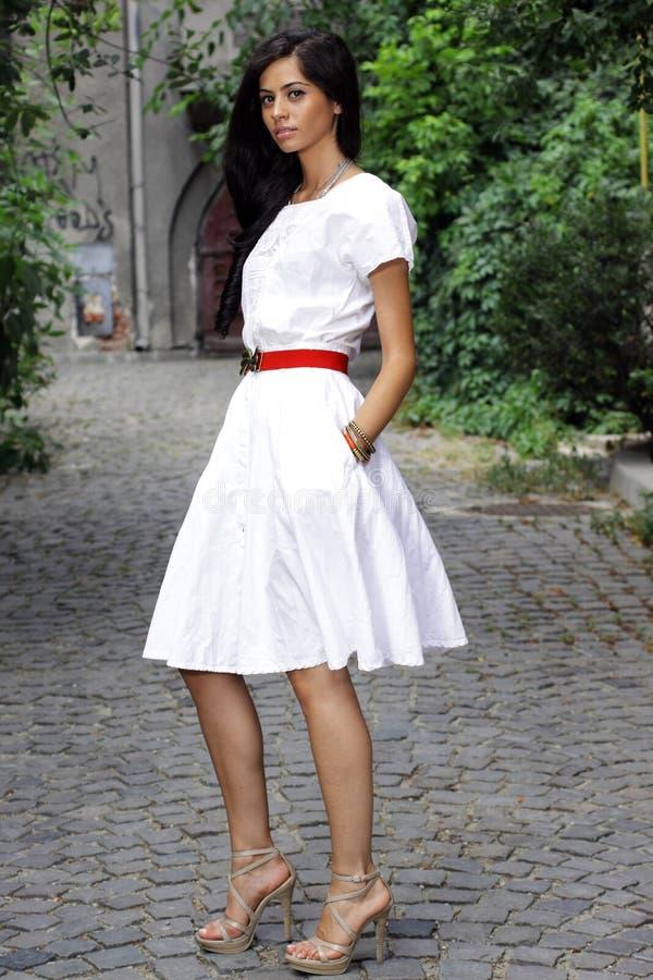 Het donkerbruine meisje van Nice in witte kleding royalty-vrije stock afbeelding