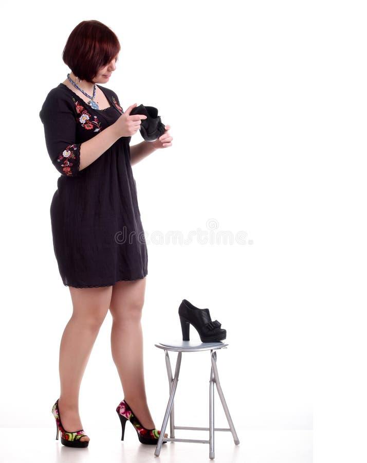 het donkerbruine meisje in zwarte kleding onderzoekt zwarte schoenen royalty-vrije stock foto