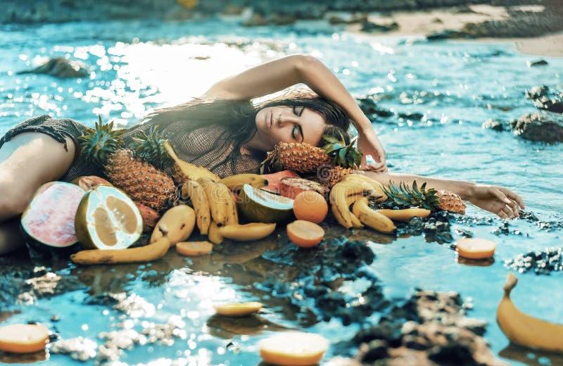 Het donkerbruine model stellen met veel gezond tropisch fruit royalty-vrije stock afbeeldingen