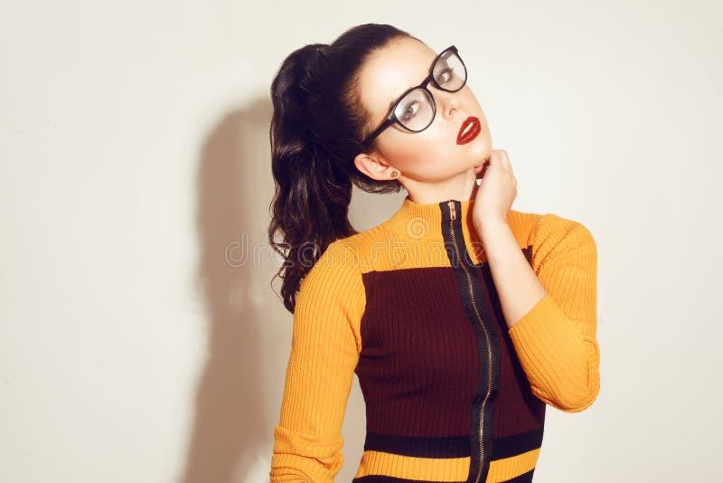 Het donkerbruine modelmeisje die van de schoonheidsmanier modieuze glazen dragen Sexy vrouw met perfecte make-up, in oranje en ro royalty-vrije stock afbeeldingen