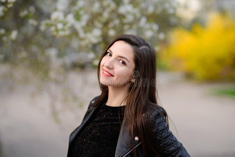 Het donkerbruine stellen in de de herfsttuin Het jonge mooie donkerbruine glimlachen outdoors Bomen met groene bladeren Tuin, Par royalty-vrije stock afbeelding