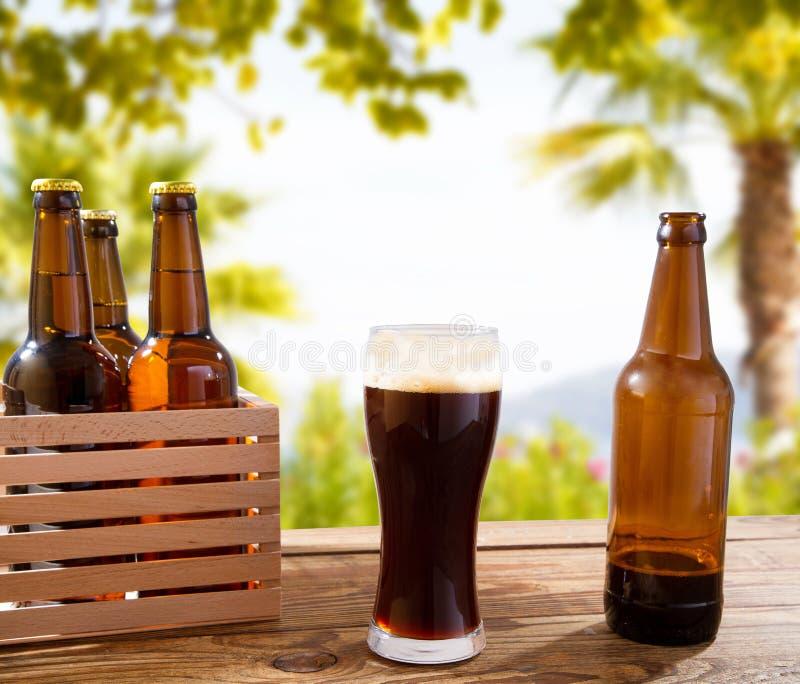 Het donkere bierglas op houten lijst met flessen, vage strand en palmenachtergrond, voedsel en drankconcept, kopieert ruimte, sel royalty-vrije stock afbeelding