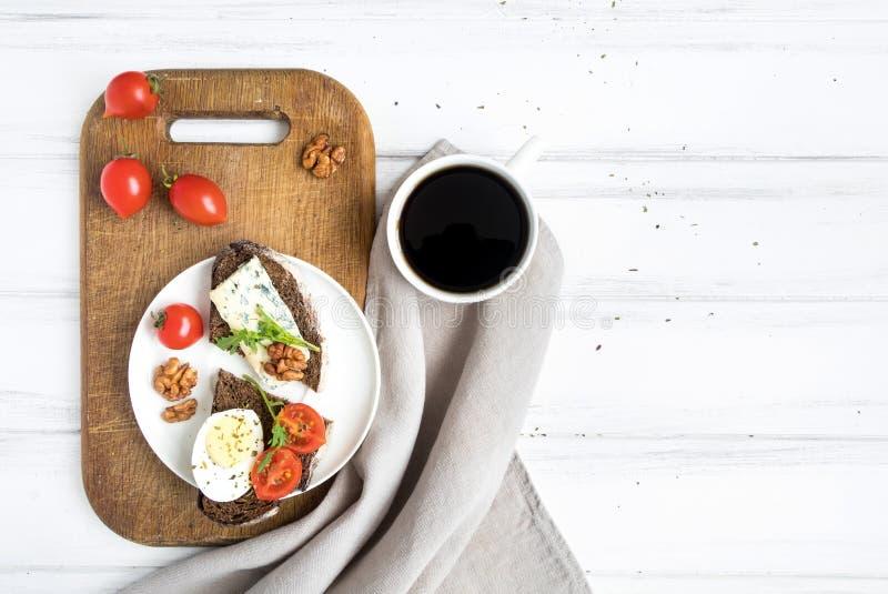 Het donkere gesneden brood, de tomaten, de eieren en een kop van koffie op houten scherpe raad verfraaiden met noten Vlak leg, ho stock afbeeldingen