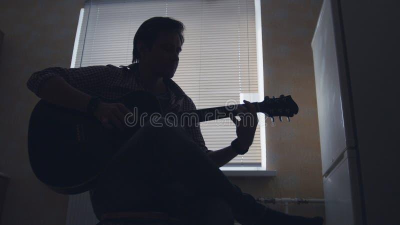 Het donkere silhouet van jonge aantrekkelijke mensenmusicus stelt muziek op de gitaar en de spelen, silhouet samen stock foto