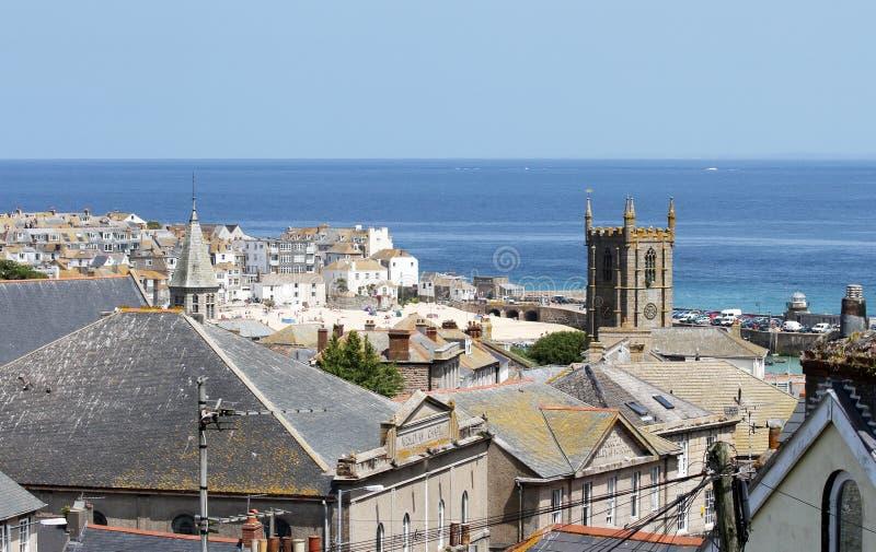 Het Dorp van de kust van St Ives, Cornwall, het UK Mening over oude stad met typische huizen en de kerk van Heilige ives in de mi stock foto