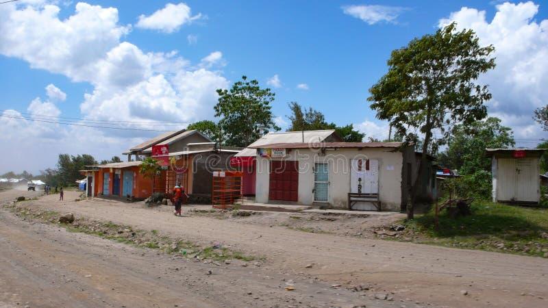 Het dorp van het land van gerecycleerde materialen op de kant van de weg in Tanzania met winkels en kleine huizen voor plaatselij royalty-vrije stock foto's