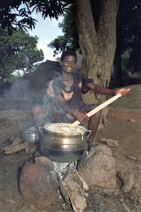 Het dorpsleven met kokende Ghanese jonge vrouw royalty-vrije stock afbeeldingen