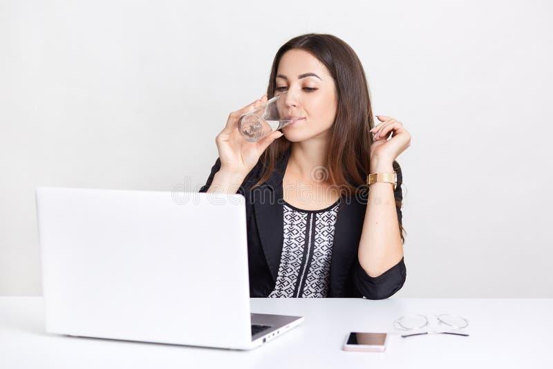Het dorstige meisje drinkt water van glas, gebruikt laptop computer voor het blogging in netwerken, let op film die, met draadloo stock afbeelding