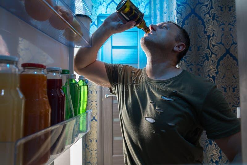 Het dorstige mens gulping onderaan een koud bier stock afbeeldingen