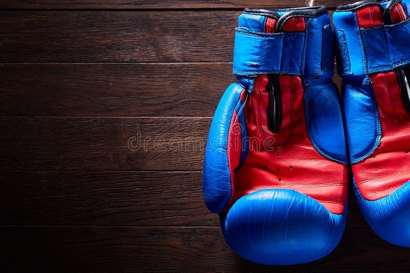 Het in dozen doen van blauwe en rode handschoenen die van kabels op een houten achtergrond hangen stock afbeeldingen