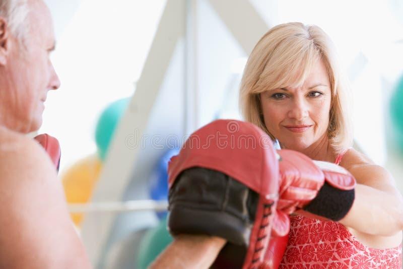 Het In dozen doen van de vrouw met Persoonlijke Trainer bij Gymnastiek