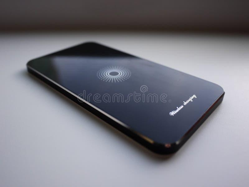Het draadloze laden voor smartphone Smartphone wordt geladen indien gezet op de oppervlakte van de post details stock fotografie