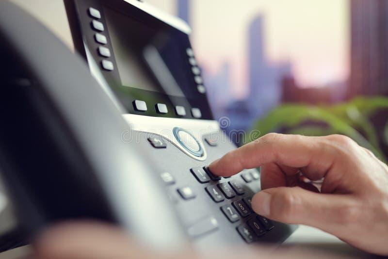 Het draaien van een telefoon in het bureau royalty-vrije stock fotografie