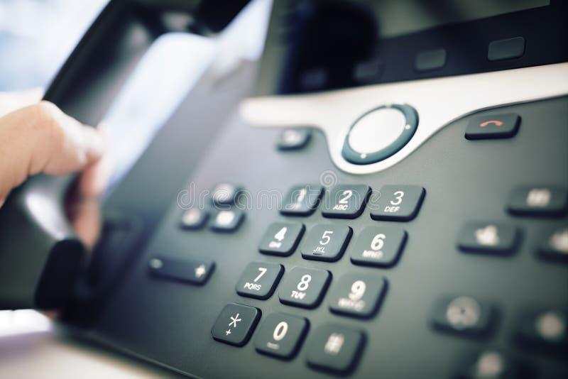 Het draaien van een telefoon in het bureau royalty-vrije stock afbeelding