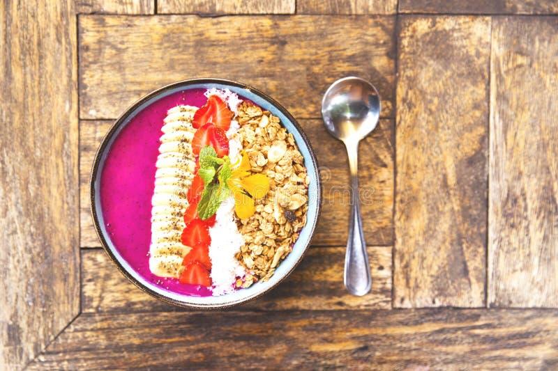 Het draakfruit smoothie werpt met aardbeien, granola, chiazaden en banaan stock afbeelding