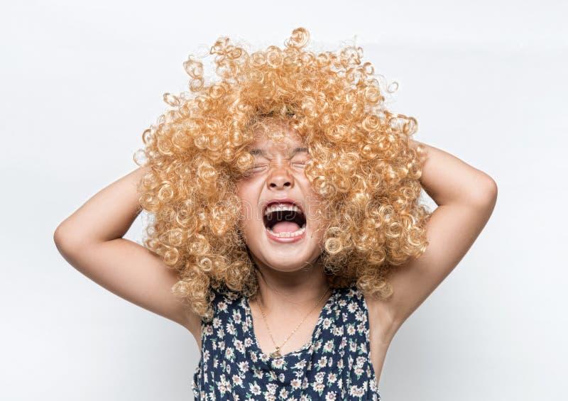 Het dragen van een blondepruik en een grappig gelaatsuitdrukking Aziatisch meisje royalty-vrije stock foto