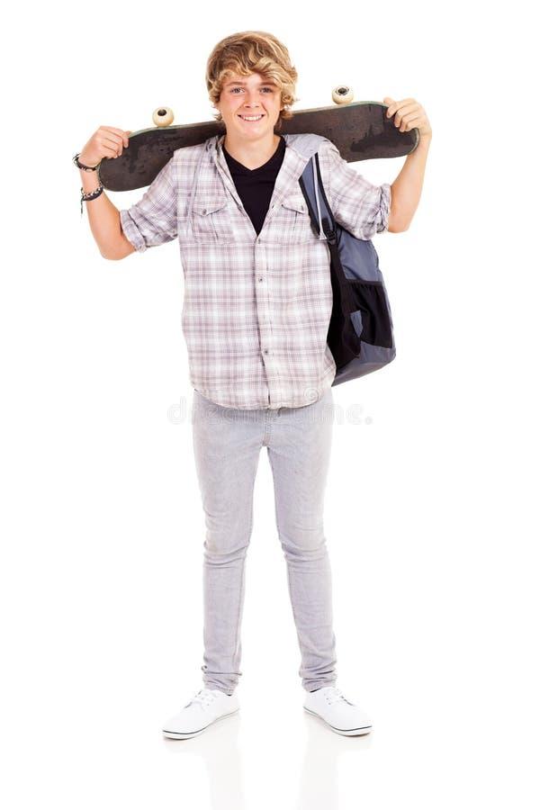 Het dragende skateboard van de tiener stock fotografie