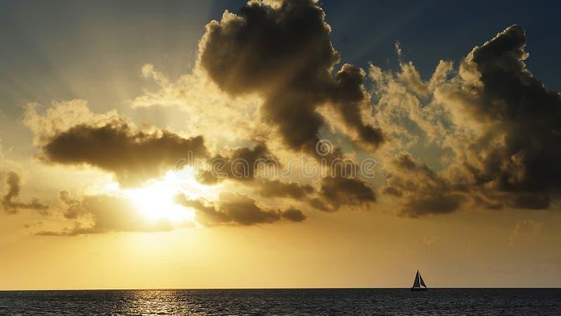 Het dramatische lichte doordringen door de wolken en het raken van het overzees stock foto
