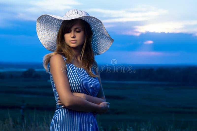 Het dramatische portret van een mooi meisje in een hoed op het gebied, een jonge vrouw loopt in openlucht in de zomer royalty-vrije stock foto