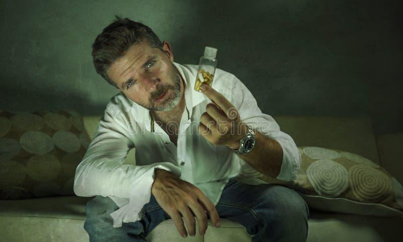 Het dramatische portret van jonge aantrekkelijke gedeprimeerde en verspilde pillen wijdt de mens die de kalmerende zitting van de stock afbeelding
