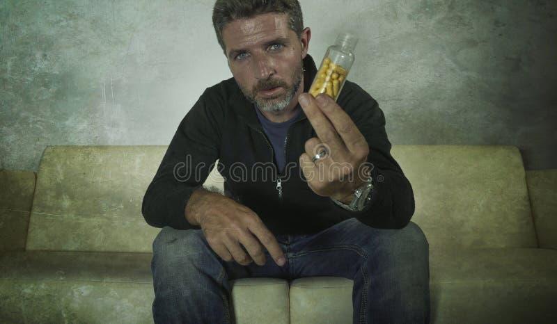 Het dramatische portret van jonge aantrekkelijke gedeprimeerde en verspilde pillen wijdt de mens die de kalmerende zitting van de stock foto's