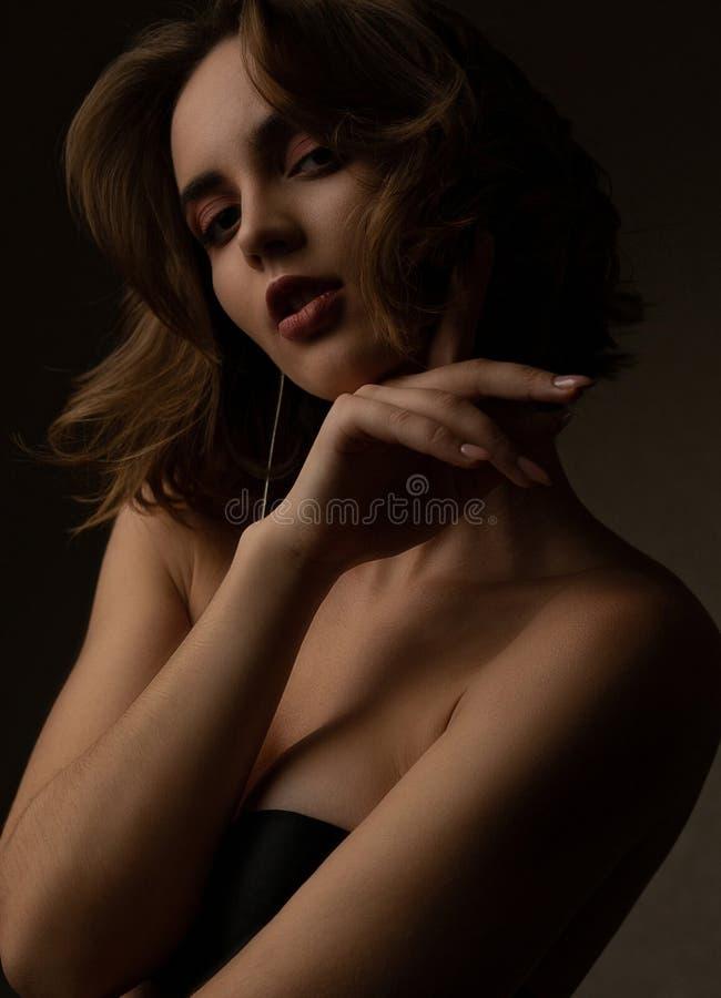 Het dramatische portret van sensueel donkerbruin model met golvend haar draagt bustehouder, die in de schaduwen stellen stock afbeelding