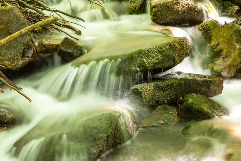 Het draperende vlotte water van de watervalclose-up zeer met natte rotsen stock foto