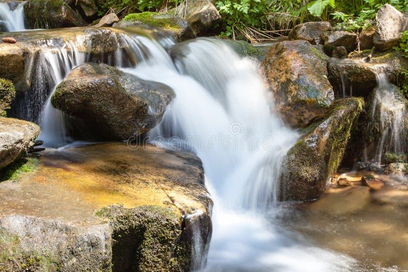 Het draperende vlotte water van de watervalclose-up zeer met natte rotsen royalty-vrije stock afbeelding