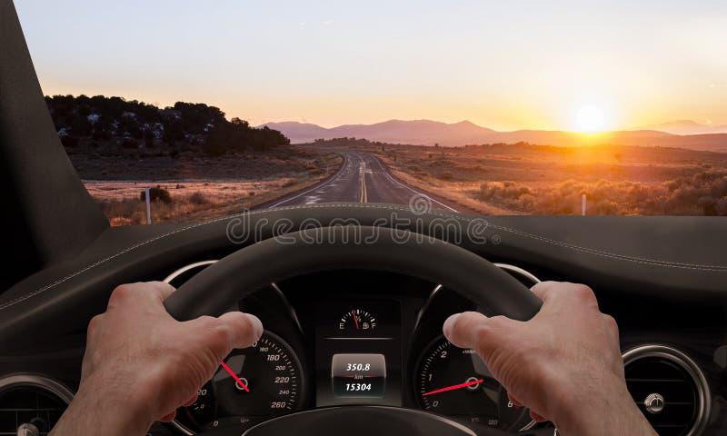Het drijven bij zonsondergang Mening vanuit de bestuurdersinvalshoek terwijl handen op het wiel stock foto