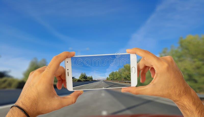 Het drijven en telefoonsconcept Handen die een smartphone houden, die een foto op de achtergrond van de onduidelijk beeldweg neme vector illustratie