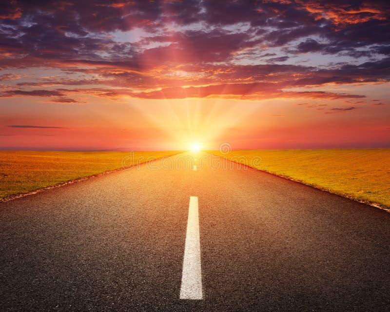 Het drijven op een lege asfaltweg bij zonsondergang stock fotografie