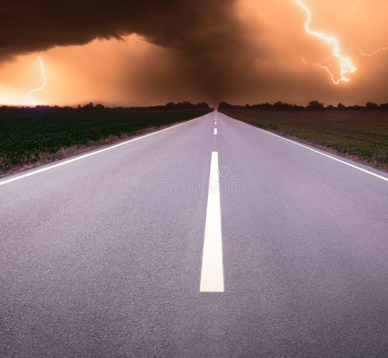 Het drijven op een lege weg naar tornado en bliksem stock fotografie