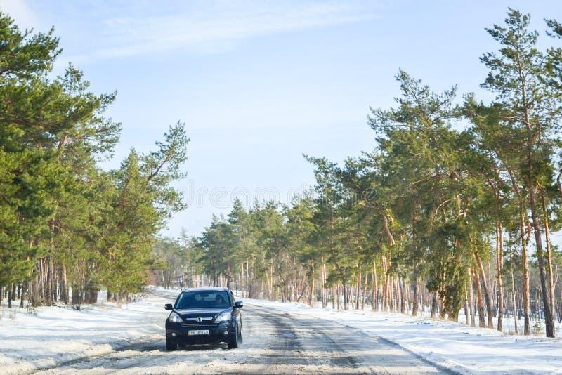 Het drijven op een sneeuwweg in de winter of de vroege lente Weergeven van het autoraam op de weg met smeltende sneeuw op het royalty-vrije stock foto
